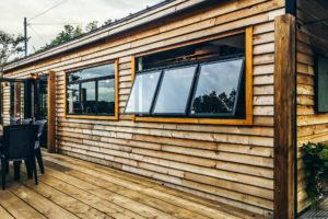 木板貼りの外壁と突き出し窓のあるテラス