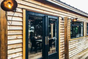 木板貼りの外壁とスチールのガラスドア